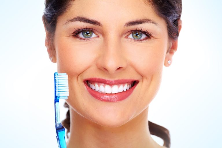 a smiling woman holding a toothbrush