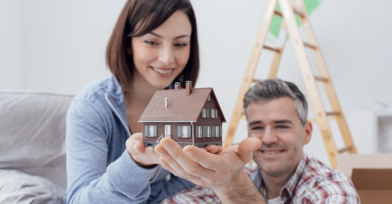 couple holding a small house