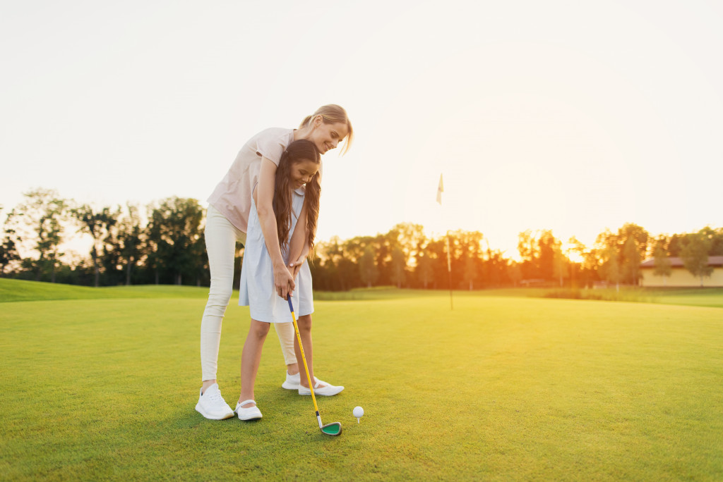 mother playing golf with daughter